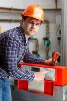 engenheiro que ajusta o trabalho de aquecimento no painel de controle automatizado