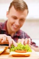 Close up of man decorating bread with lettuce photo