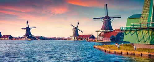 panorama de auténticos molinos de zaandam en el canal de agua