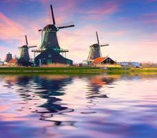 authentieke zaanse molens aan de waterkanaal in zaanstad.