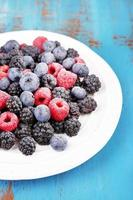 Iced berries on plate, on color wooden background photo
