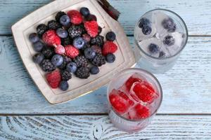 Frozen berries and ice cubes, raspberry and blueberry on table photo