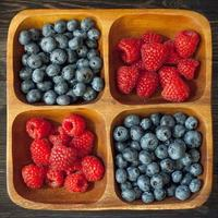 Wooden bowl of raspberries and blueberries