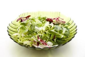 Fresh mixed salad in glass bowl photo