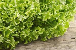 Fresh green lettuce salat on wooden background. Healthy food