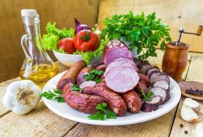Table plate sliced sausages vegetables