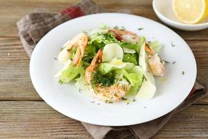 Salad with shrimps, lettuce and cheese on a white plate photo