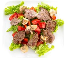 Vegetable salad with mashrooms and meat isolted on white background photo