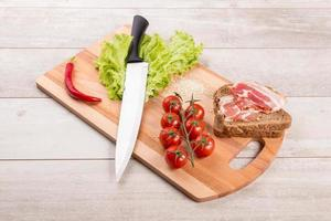Tomato, toasts, meat and salad on wooden table photo