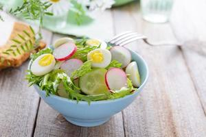 Spring salad from fresh vegetables and quail eggs