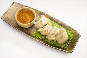 Traditional Dumpling Momos Served With Tomato Sauce photo