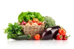 Verduras dispuestas en una cesta sobre un fondo blanco.