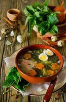 Nettle soup with eggs and carrot in the bowl photo