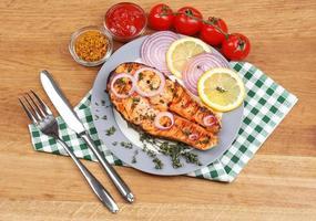 saboroso salmão grelhado com legumes, na mesa de madeira