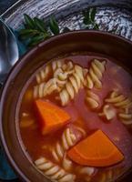 Sopa de tomate fresco en un tazón de gres foto