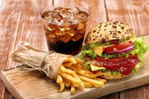 Grilled hamburger with fries and cola on brick wall background