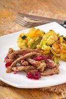 Stroganoff de ternera con salsa de arándanos y verduras a la parrilla foto