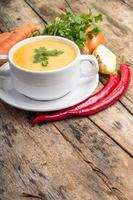 alimentos orgánicos. sopa de guisantes con verduras alrededor sobre fondo de madera foto