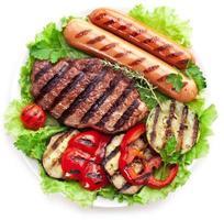 bistec a la parrilla, salchichas y verduras.