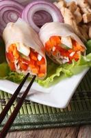 Sliced spring rolls with chicken on a plate close-up. Vertical photo