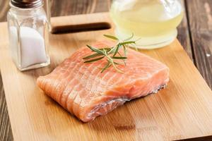 Raw salmon filet on wooden cutting board photo