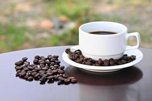 xícara de café quente e grãos de café, deitado sobre mesas de madeira.