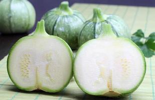 Round zucchini on a green bamboo tablecloth