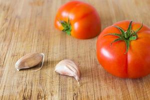 Tomatoes and garlic on a cutting board photo