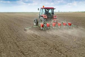 Farmer sowing crops with pneumatic seeding machine photo