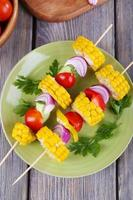 Sliced vegetables on wooden picks on plate on table close-up