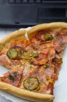 pieces pizza on laptop keyboard background photo