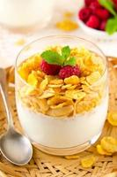 Breakfast with cereal flakes, yogurt and fresh raspberries photo