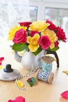 Colorful roses in a tea can photo