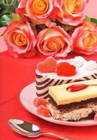 Valentine cakes, tarts and red roses on the red tablecloth