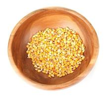 Corn in wooden bowl isolated on white photo