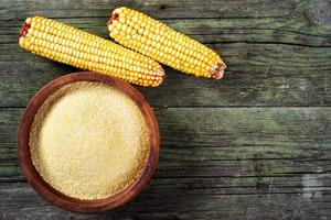 Maize, meal and ceramic bowl on wooden table