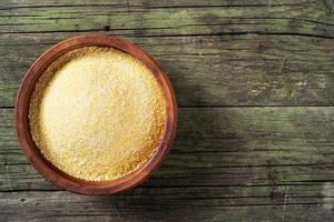 harina de maíz y tazón de cerámica en mesa de madera foto