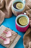 Two blue cup of tea in knitted sweater with hearts