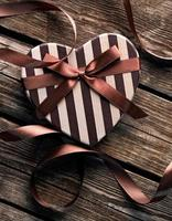 Heart-shaped Valentines Day gift box on wooden plates.