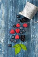 Summer berries on a blue background. Top view, vertical photo