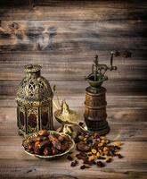 Oriental lantern and mill. Raisins and dates on wooden background