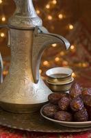 uma jarra de café e um prato de tâmaras