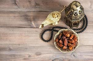 Ramadan lamp, rosary and dates on wooden background