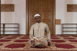 moslim man in dishdasha leest de koran