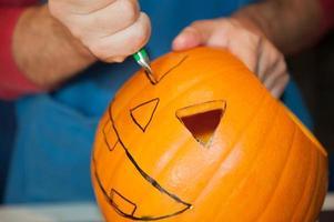man prepares a pumpkin for Halloween