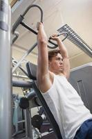 Fit man using weights machine for arms photo