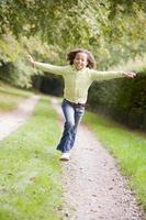 Young girl running on a path outdoors smiling photo