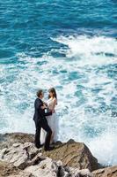 Bride and groom near the ocean photo