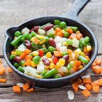 Mixed vegetable meal in old frying pan closeup and ingredients
