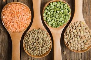 Four wooden spoons with dried peas and lentils